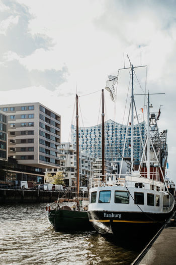 Sailboats moored on harbor in city against sky