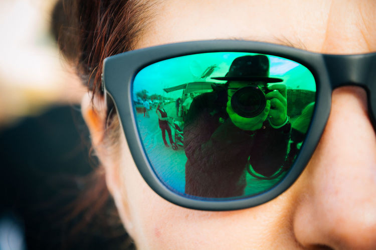 Cropped image of woman with photographer reflecting on sunglasses