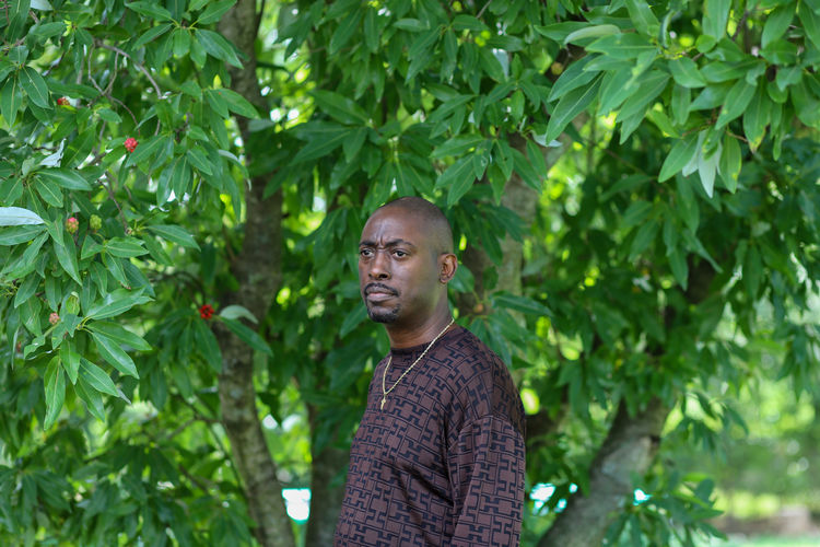 Portrait of young man standing against tree