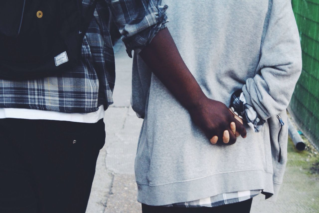 Midsection of interracial couple holding hands on street