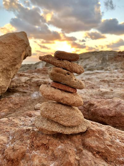 Stack of stones on beach during sunset