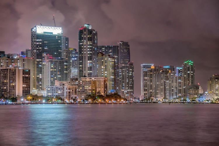 Sea and illuminated buildings against cloudy sky