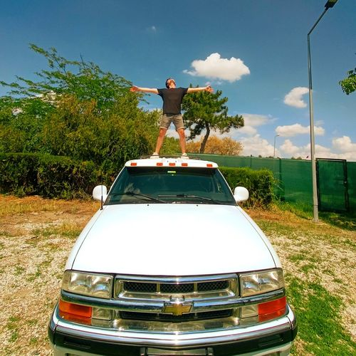 Man standing by car against sky