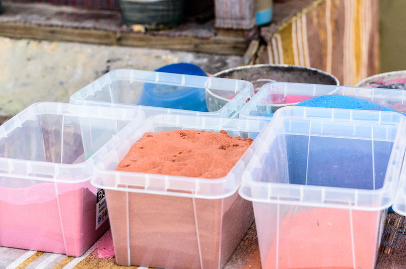 High angle view of powder paint in containers on table