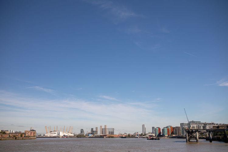 Sea by buildings against blue sky