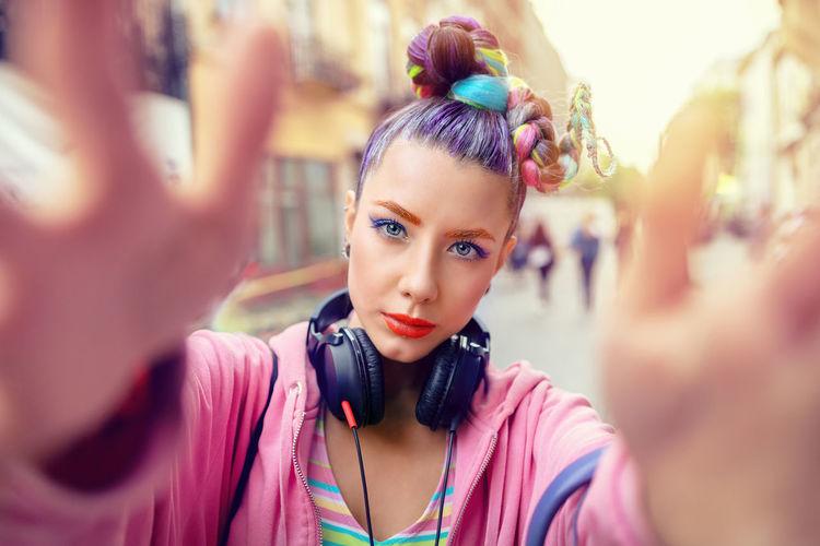 Funky gen z girl with trendy rebel look taking selfie in city street