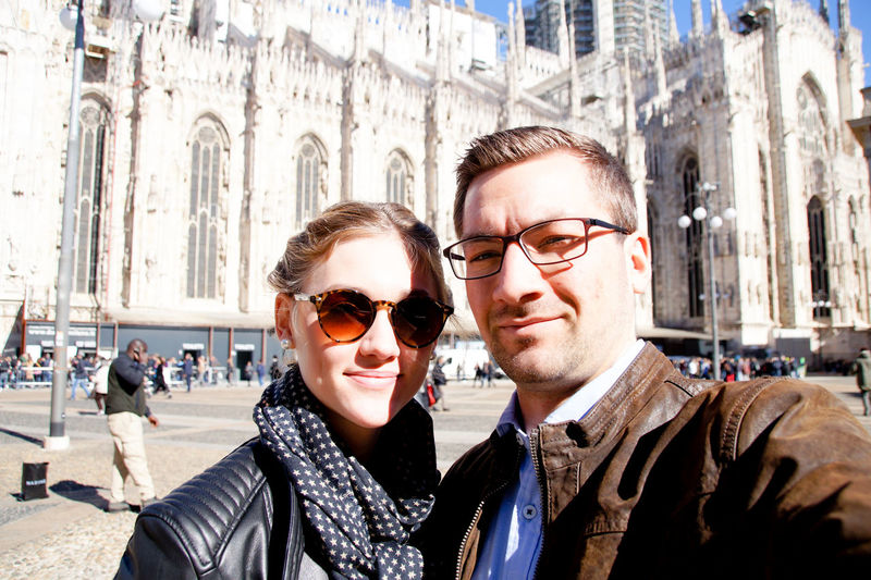 Portrait of couple standing against milan cathedral on sunny day