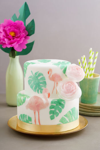 Two tiered tropical wedding cake with fondant, tropical wafer paper leaves and flamingos with ranunculus flowers on golden cale platter Flamingo Wedding Cake Paper Flower Paperflower Party Tropical Tropical Wedding Cake Wafer Paper Waferpaper Wedding Cake
