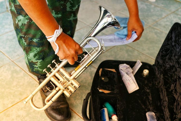 Low section of person holding musical instrument