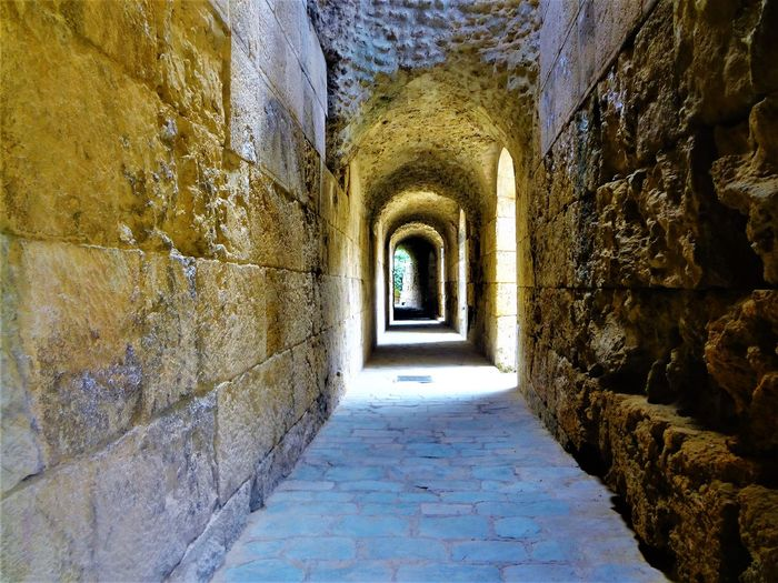 Ancient Ancient Civilization Arcade Arch Architecture Building Built Structure Corridor Day Diminishing Perspective Direction Empty History Indoors  Light At The End Of The Tunnel Long No People Old Stone Wall The Past The Way Forward Wall Wall - Building Feature