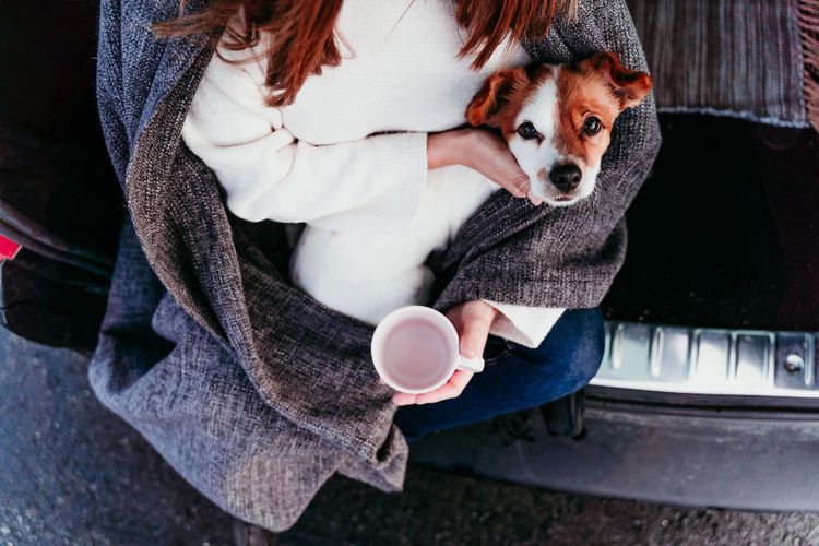 Midsection of woman with dog and coffee