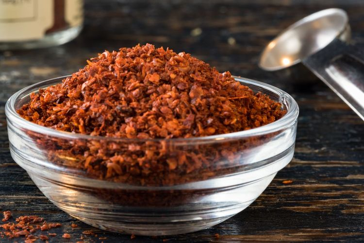 Close-up of ground aleppo peppers in bowl on table