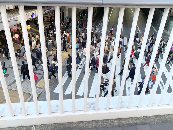 High angle view of people standing by railing in city
