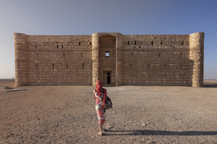 Rear view of woman walking towards built structure