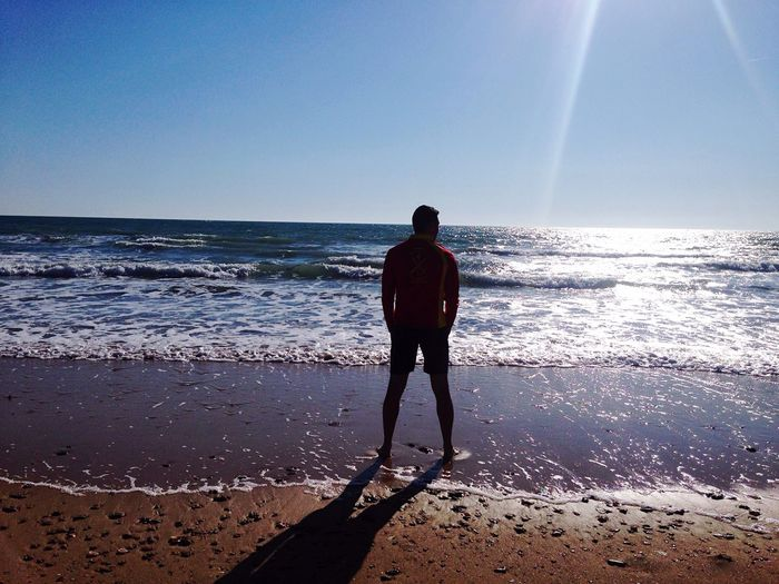 Rear view full length of man standing at beach against sky on sunny day
