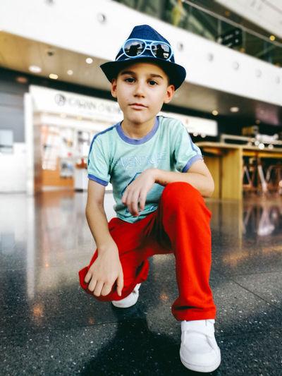 Portrait of boy crouching at mall