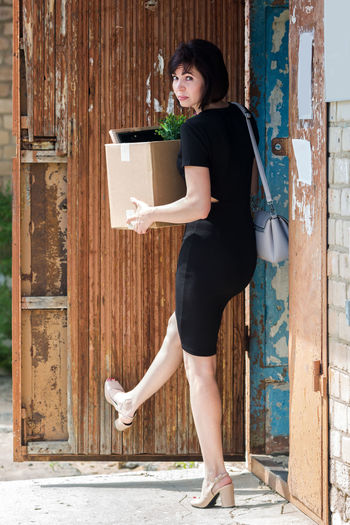 Portrait of woman carrying box