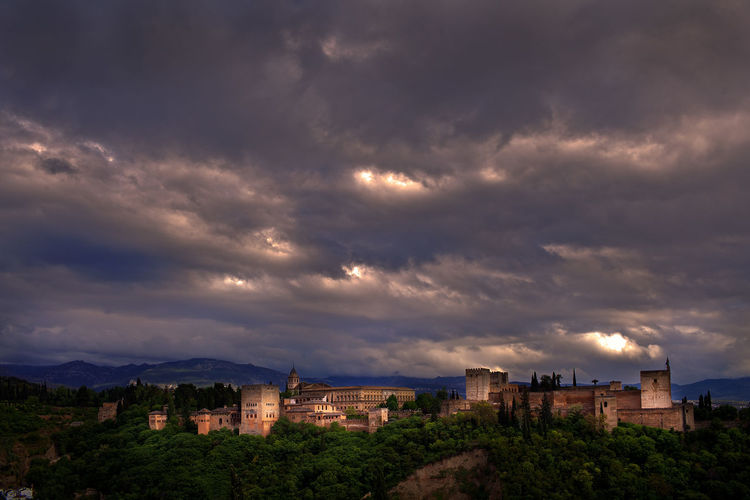 Alhambra palace against cloudy sky in stormy weather