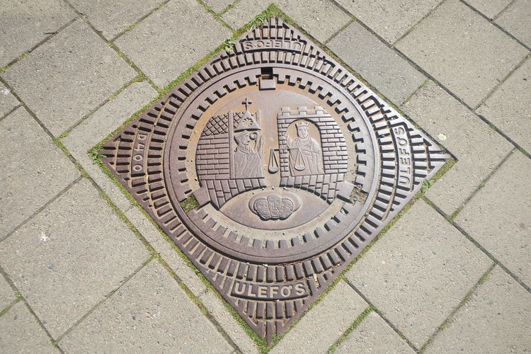 High angle view of manhole on tiled floor