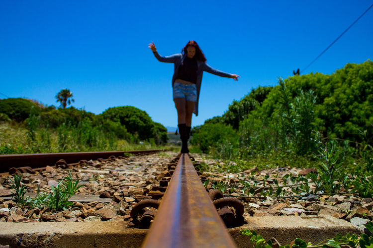 Rear view of person standing on railroad track