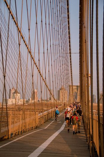 People on brooklyn bridge against sky