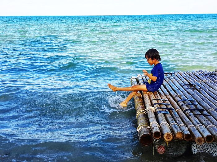 Boy sitting on wooden raft over sea
