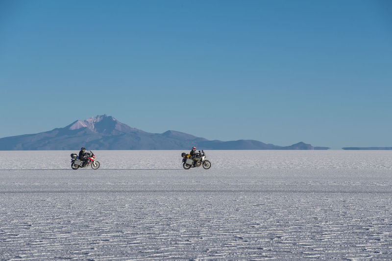 People riding motorcycle on landscape against clear blue sky