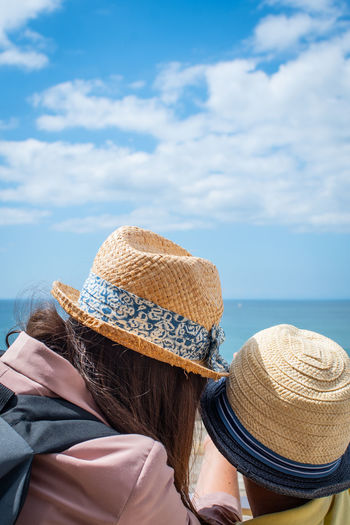 Rear view of woman and boy looking at sea against sky