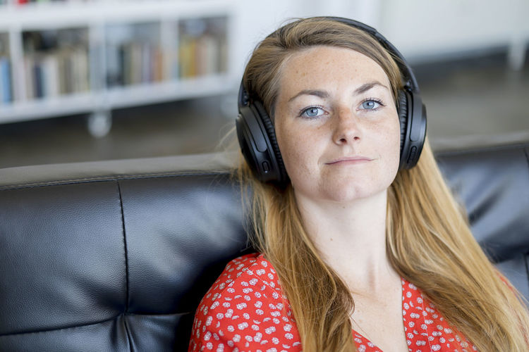 Portrait of young woman listening music at home