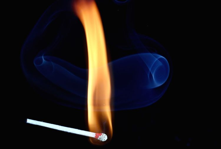 Close-Up Of Burning Match Against Black Background
