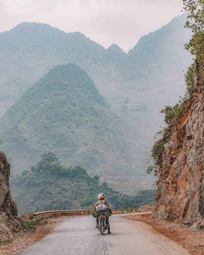 Rear view of man riding motorcycle on mountain road