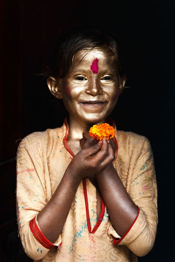 Portrait Of Boy With Face Paint Holding Marigold Against Black Background
