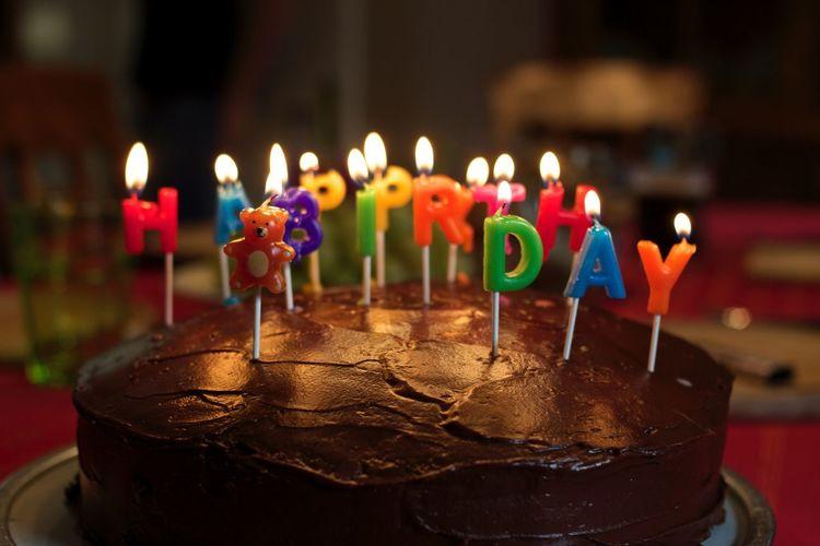 Close-Up Of Illuminated Birthday Candles On Cake