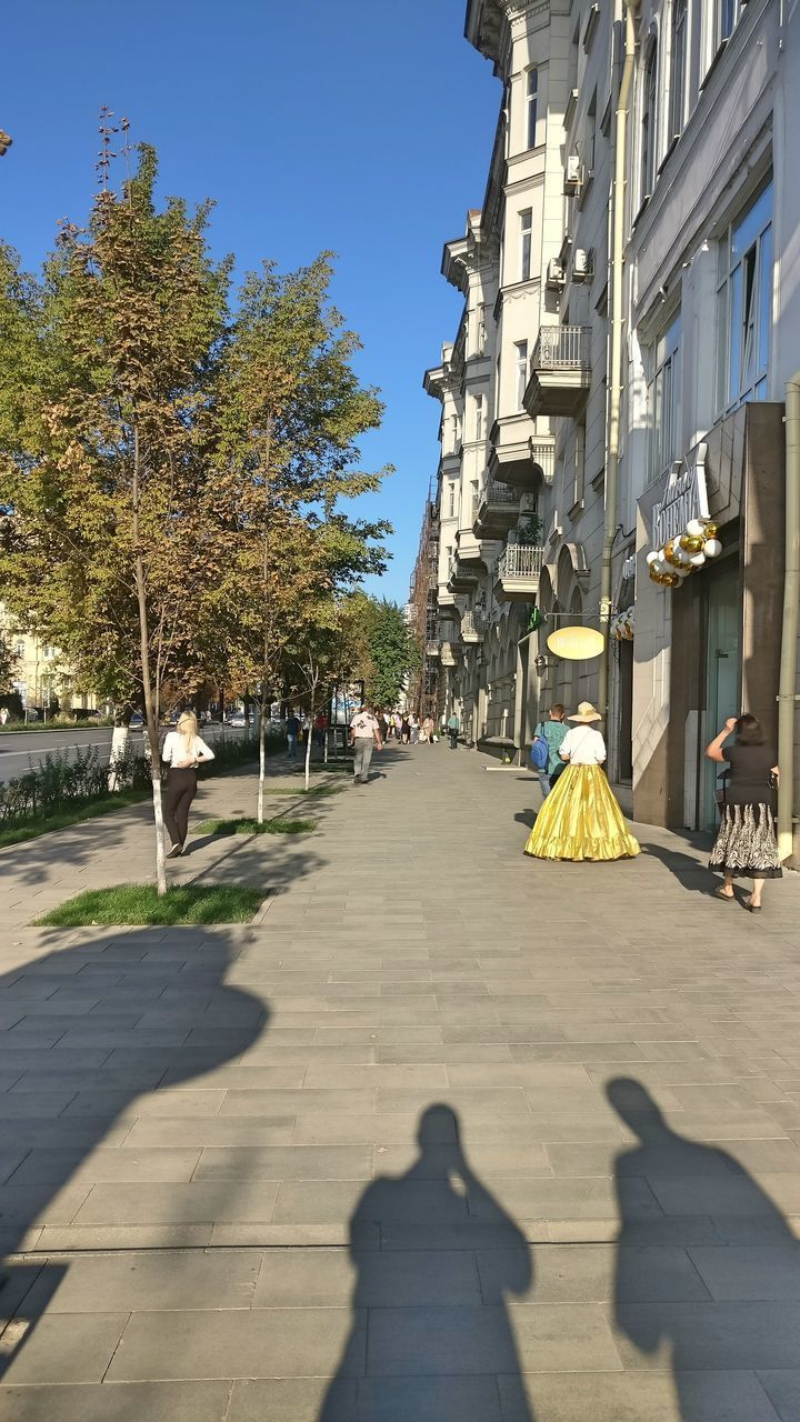 shadow, sunlight, architecture, tree, built structure, plant, nature, real people, day, building exterior, city, footpath, sky, street, incidental people, group of people, building, men, lifestyles, women, outdoors