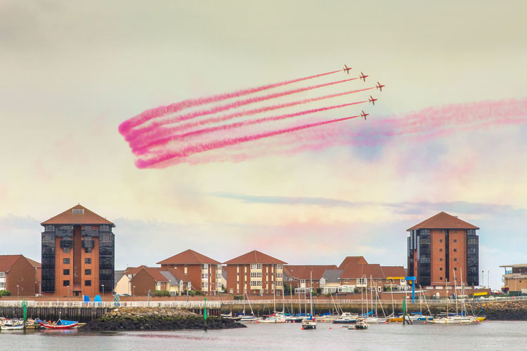 Fighter Planes Performing Airshow River And Buildings