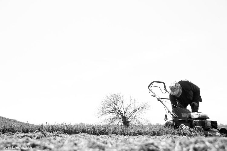 Man with lawn mower on field against clear sky