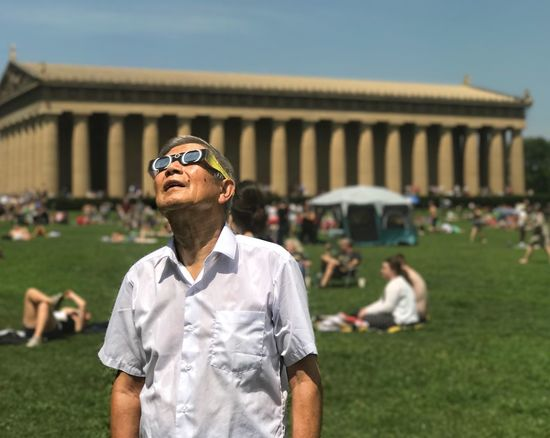 Asian man watches total solar eclipse in Nashville's Centennial Park. Eclipse Eclipse 2017 Eclipse Of The Sun Nashville Solar Eclipse Real People Asian American Older Man Outdoors Leisure Activity Day Focus On Foreground One Person Building Exterior Architecture Grass Sky People Connected By Travel