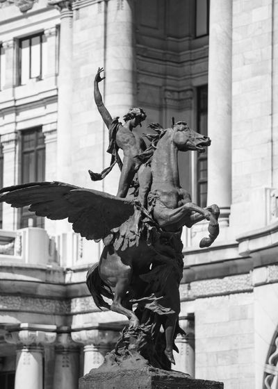 Low angle view of statue against palacio de bellas artes on sunny day