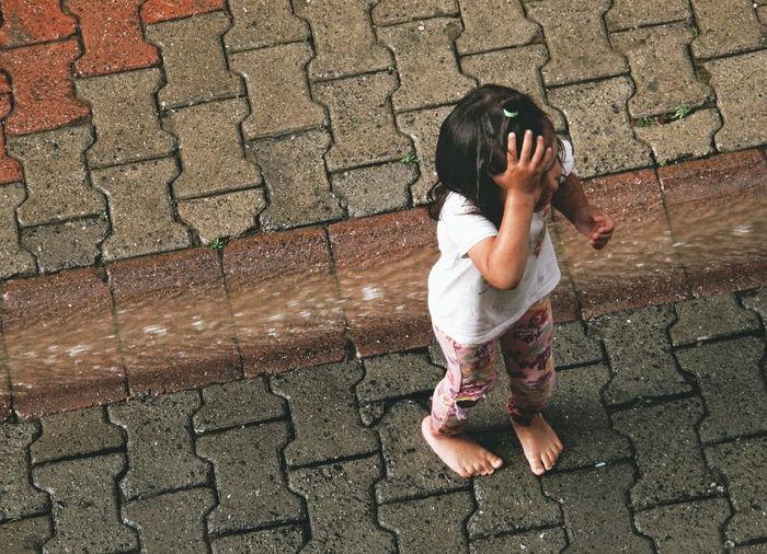 Hapiness of Rain Kid Kids Kidsphotography Rain Raining Raining Day Street Child Childhood Sidewalk High Angle View One Girl Only Footpath Children Only Garden Path Walkway Footwear Stone Tile The Photojournalist - 2018 EyeEm Awards The Street Photographer - 2018 EyeEm Awards 10 The Great Outdoors - 2018 EyeEm Awards