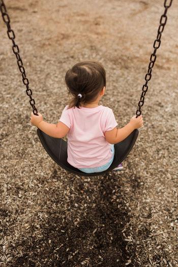 Girl playing on swing at playground