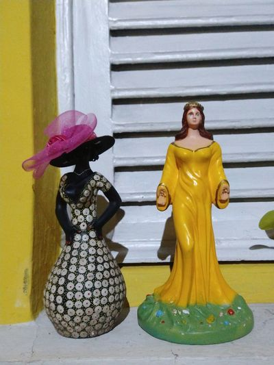 Statue of woman against yellow wall