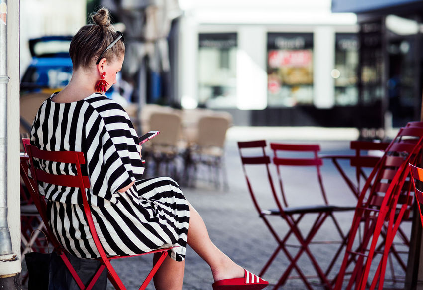 Color Matching Adult Architecture Beautiful Woman Cafe Casual Clothing Chair City Day Focus On Foreground Hairstyle Incidental People Leisure Activity Lifestyles One Person Outdoors Real People Rear View Seat Streetphotography Striped Waiting Women Young Adult