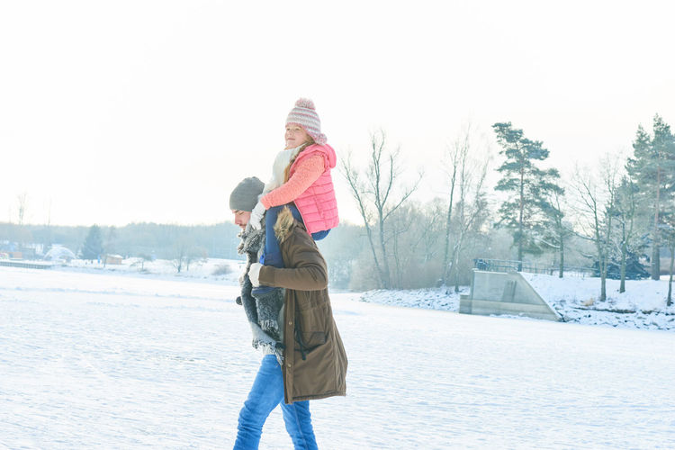 Side View Of Man Giving Piggyback To Daughter On Snow Covered Field