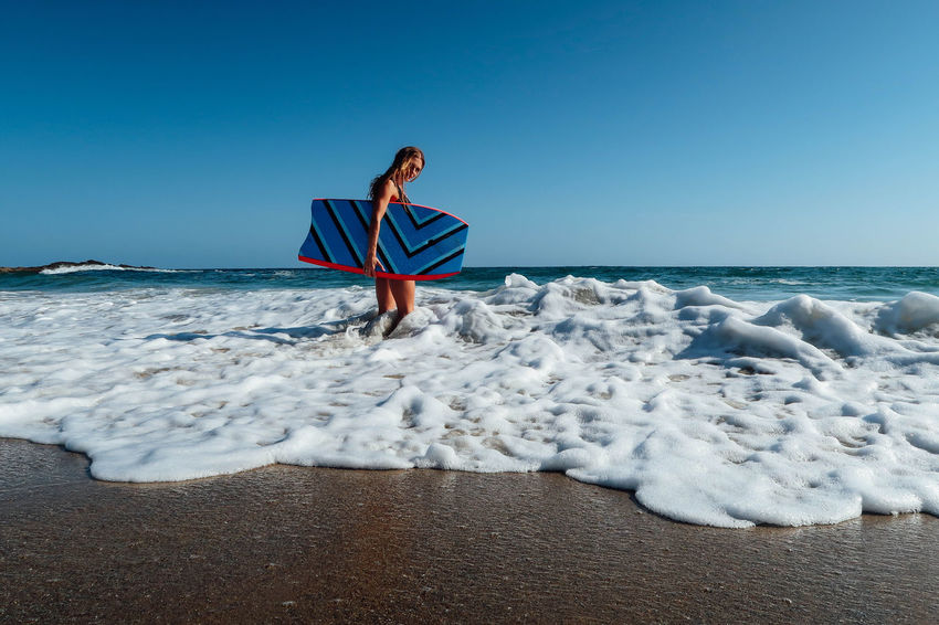Young beautiful girl with surfboard on the ocean beach Beach Beauty In Nature Bikini Blue Body & Fitness Clear Sky Day Extreme Holiday Nature Outdoors Pacific Ocean Sand Sea Summer Surf Surfboard Surfing Tropical Vacation Vacations Water The Week On EyeEm