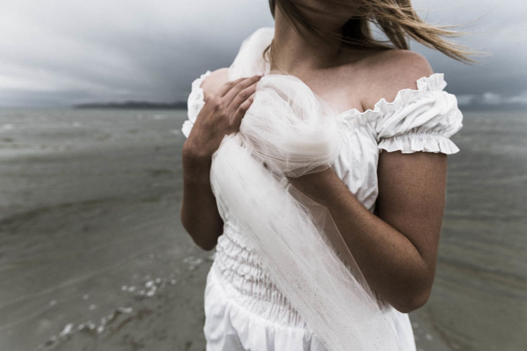 Midsection Of Bride Standing At Beach