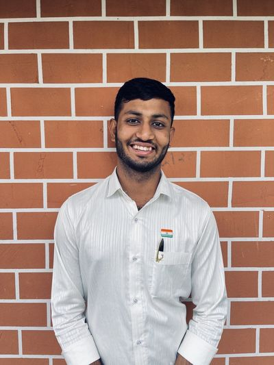 Portrait of smiling young man standing against brick wall