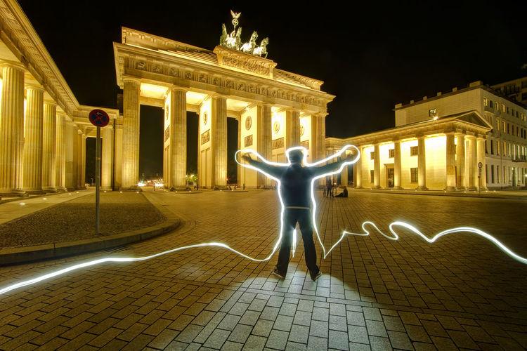 Rear View Of Man Doing Light Painting Against Brandenburg Gate During Night