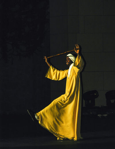 Mid section of man with arms raised standing at night