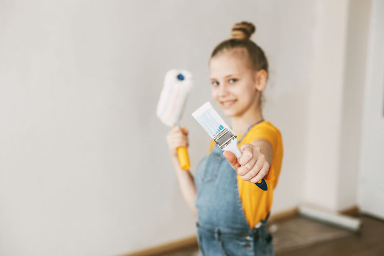 A girl in a denim overalls and a yellow t-shirt helps to paint the walls in an apartment white.