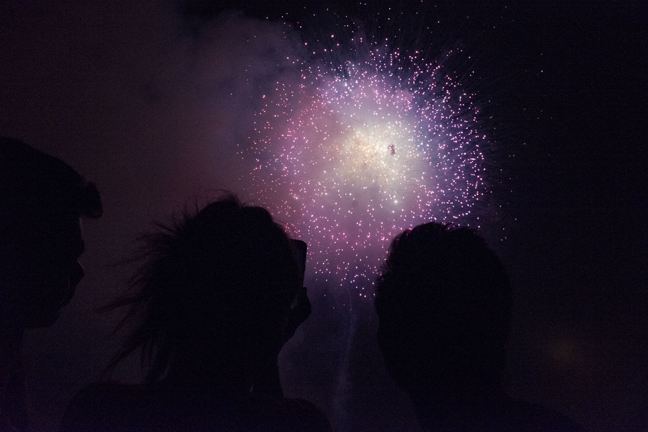 silhouette, night, real people, sky, firework display, two people, low angle view, outdoors, togetherness, nature